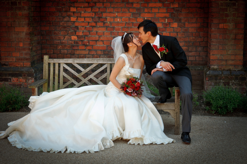 Chinese Bride and groom celebrate their wedding with a picture and a kiss in the grounds of Fulham Palace London