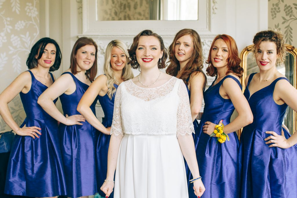 Bride poses for group portrait with her six bridesmaids